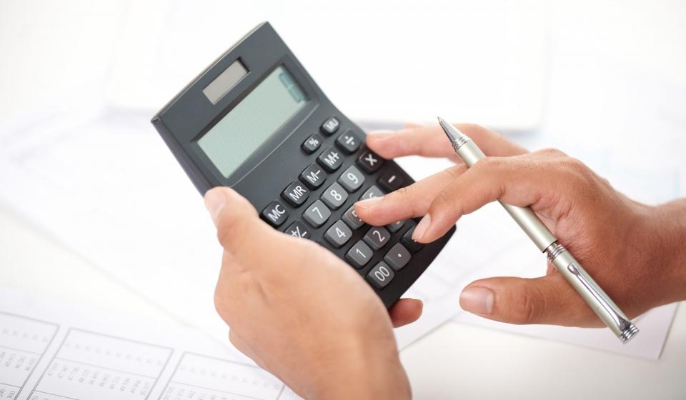 unrecognizable-office-worker-using-calculator